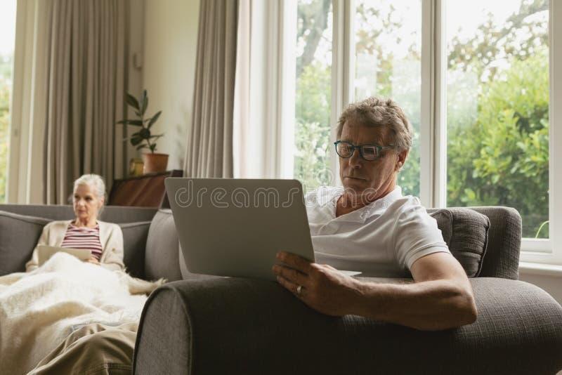 Actieve hogere mensenzitting op bank en het gebruiken van laptop in woonkamer bij comfortabel huis royalty-vrije stock foto