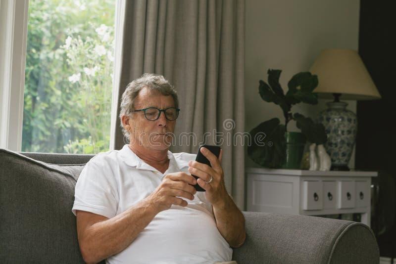 Actieve hogere mensenzitting op bank en het gebruiken van mobiele telefoon in woonkamer bij comfortabel huis royalty-vrije stock foto