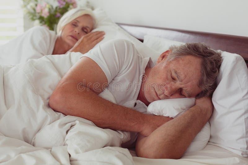 Actieve hogere paarslaap samen in bed in slaapkamer bij comfortabel huis stock fotografie