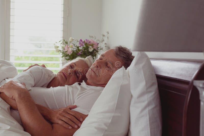 Actieve hogere paarslaap samen in bed in slaapkamer bij comfortabel huis stock foto