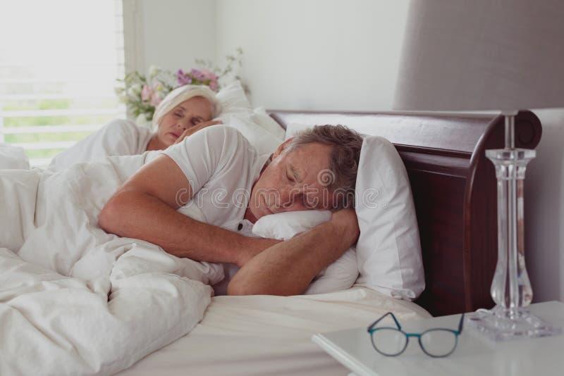 Actieve hogere paarslaap samen in bed in slaapkamer bij comfortabel huis stock afbeelding