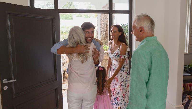 Actieve hogere vrouw die bij deur in een comfortabel huis omhelst royalty-vrije stock afbeelding