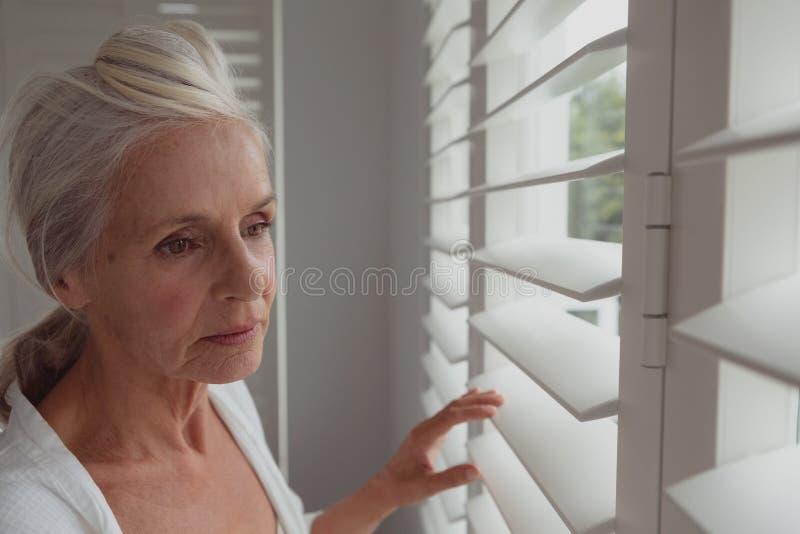 Actieve hogere vrouw die door venster in een comfortabel huis kijken stock fotografie