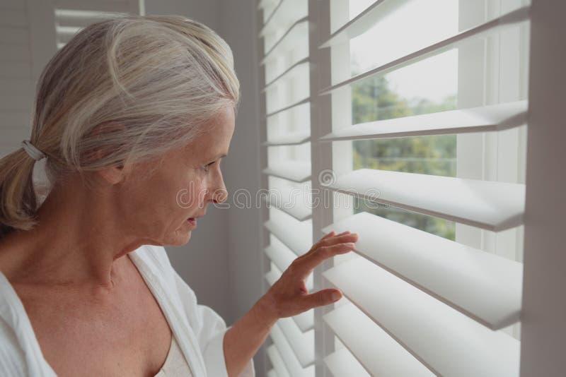 Actieve hogere vrouw die door venster in een comfortabel huis kijken stock foto's