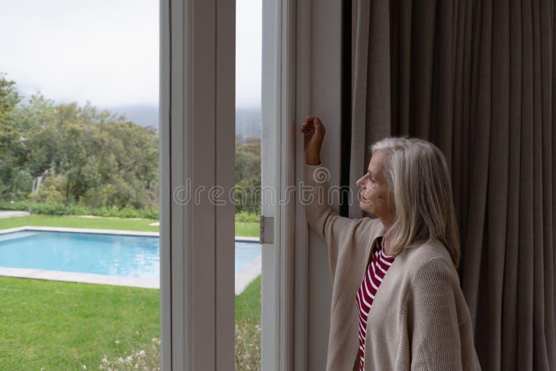 Actieve hogere vrouw die door venster in een comfortabel huis kijken royalty-vrije stock fotografie