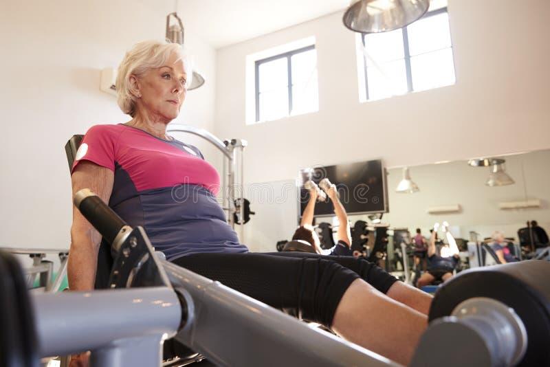 Actieve Hogere Vrouw die op Materiaal in Gymnastiek uitoefenen royalty-vrije stock fotografie
