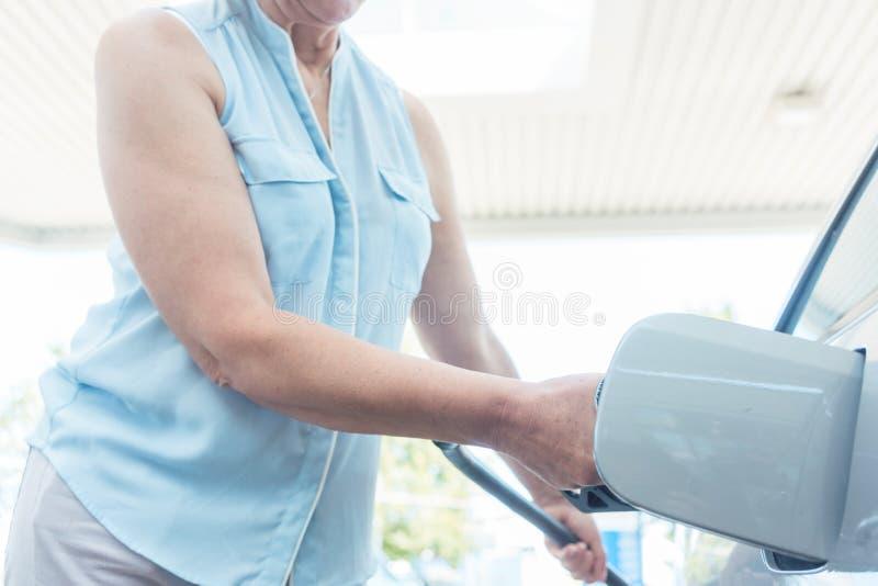 Actieve hogere vrouw die terwijl het opvullen van de gashouder van haar auto glimlachen stock fotografie