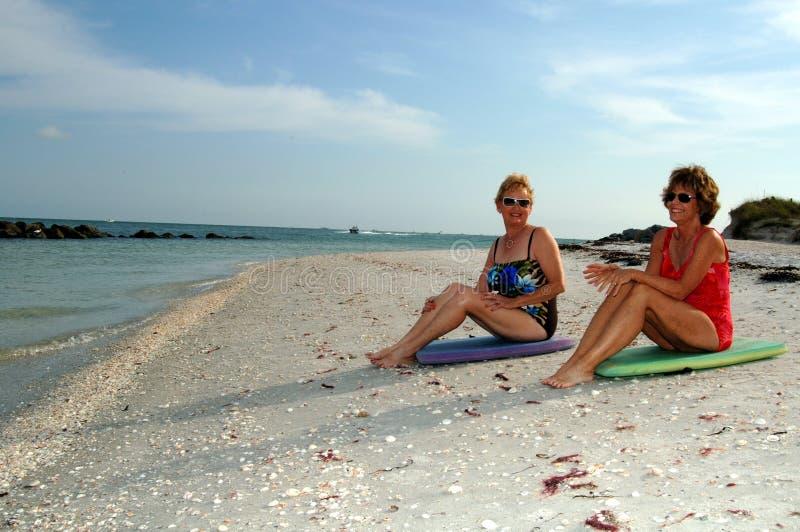 Actieve hogere vrouwen bij strand stock foto's