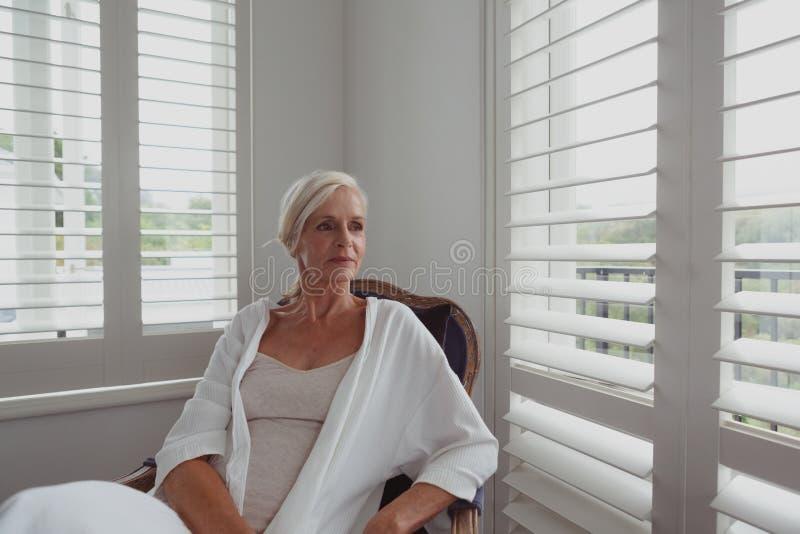 Actieve hogere vrouwenzitting op stoel in een comfortabel huis stock afbeeldingen