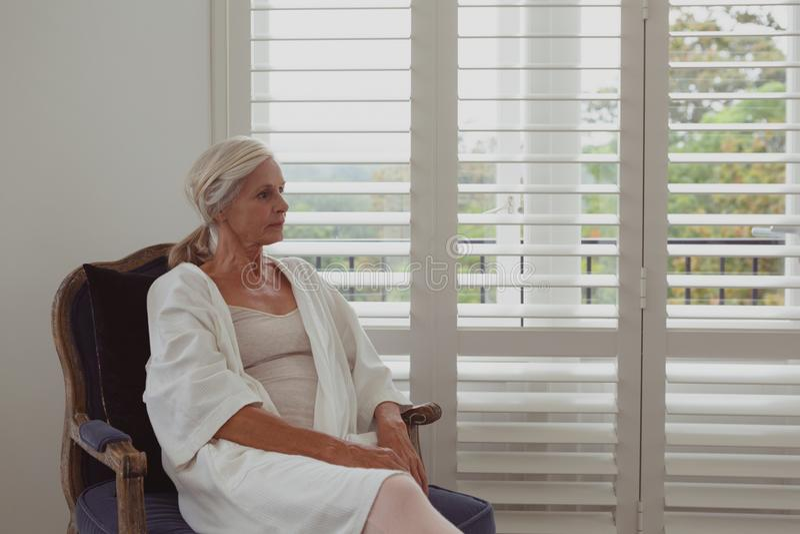 Actieve hogere vrouwenzitting op stoel in een comfortabel huis royalty-vrije stock foto