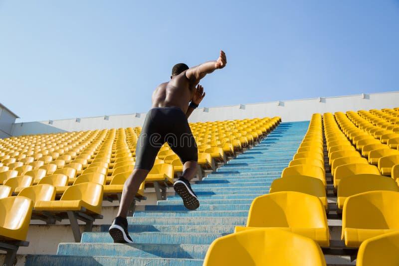 Actieve jonge Afrikaanse sportman die op de treden beklimmen royalty-vrije stock foto's