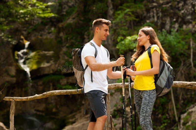 Actieve jonge cople die op een houten brifge over bergkreek wandelen stock fotografie