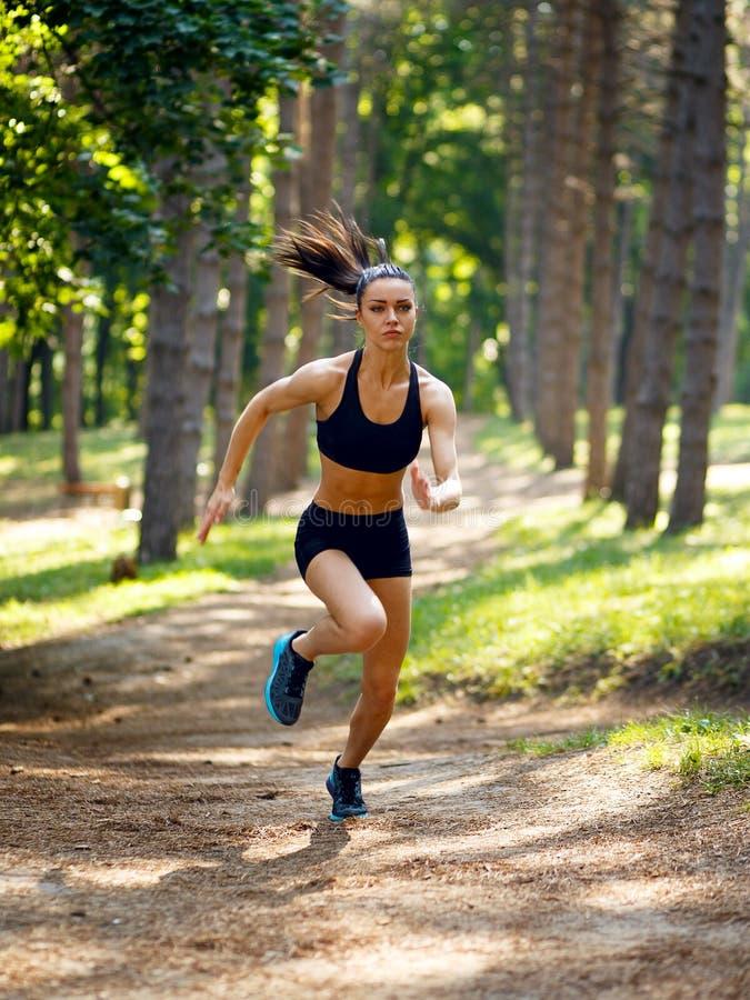 Actieve jonge donkerbruine vrouw die in park, de zomer, gezond, perfect toonlichaam lopen Training buiten Bevat gradiënt en het k royalty-vrije stock afbeelding
