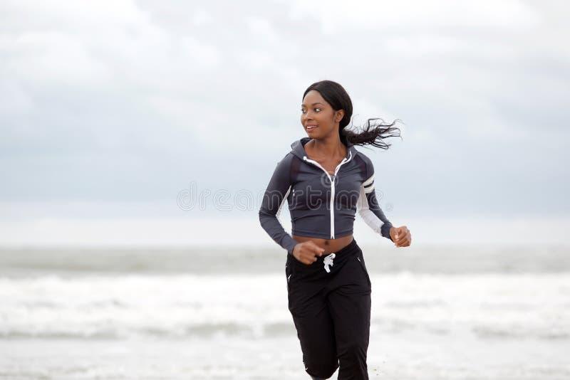 Actieve jonge vrouw die door water bij het strand lopen stock afbeelding