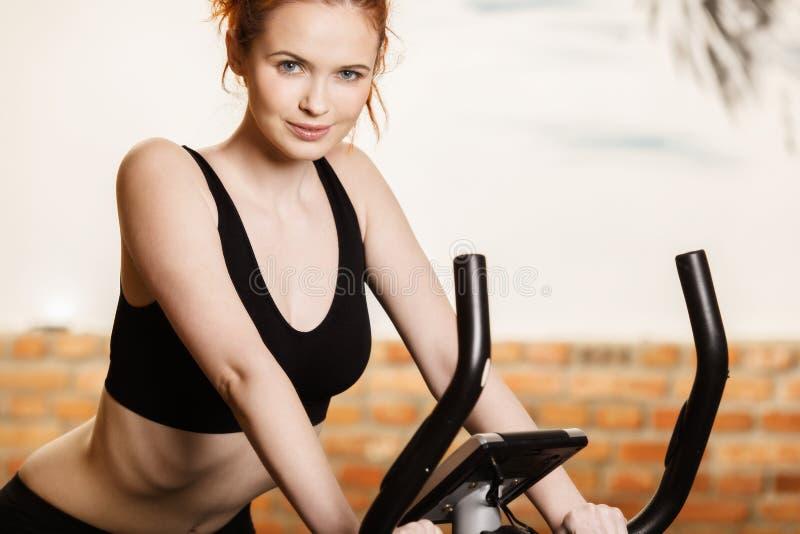 Actieve jonge vrouw die oefening op fiets thuis doen stock afbeelding
