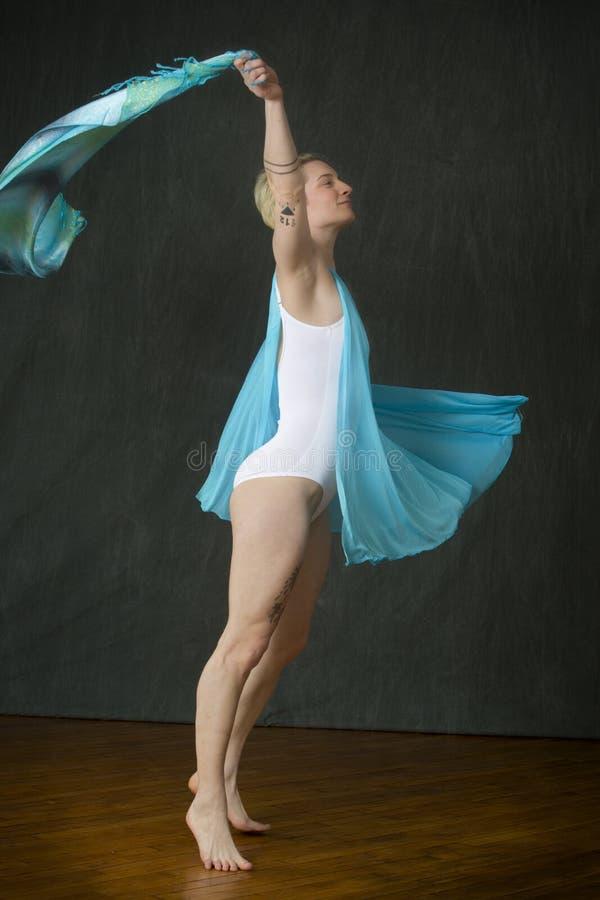 Actieve jonge vrouwendanser die blauwe sjaal in de studio werpen stock afbeeldingen