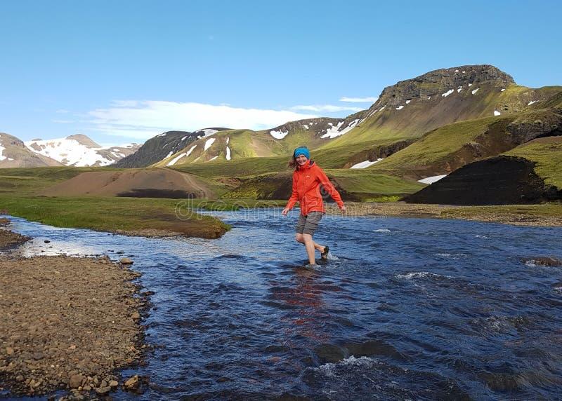 Actieve jonge wandelaarvrouw die rivier kruisen en van de bergmening over de emotiesvakanties genieten van de avonturen actieve v royalty-vrije stock foto's