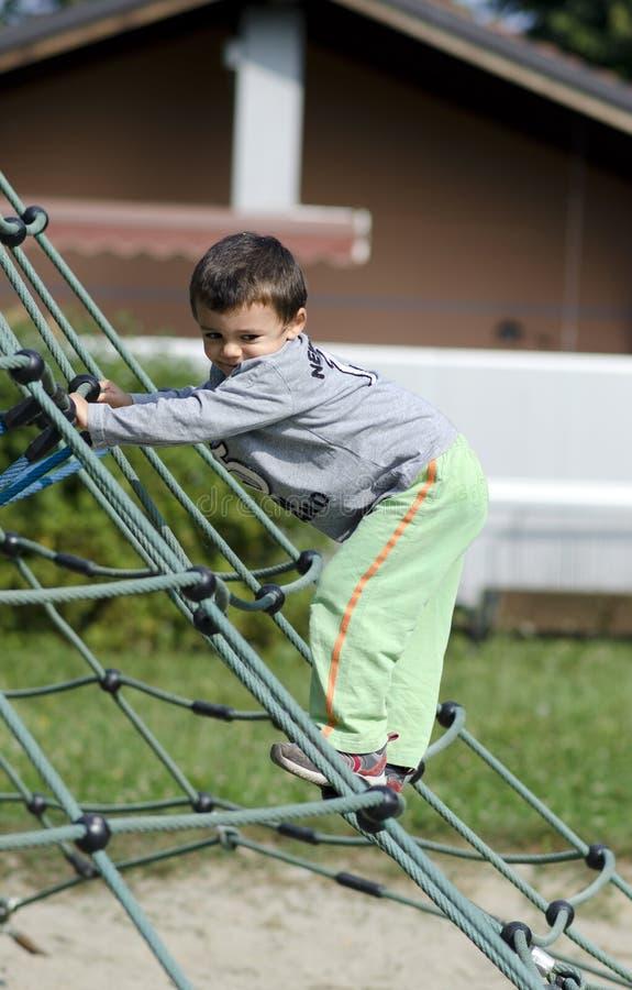 Actieve jongen in speelplaats stock foto's