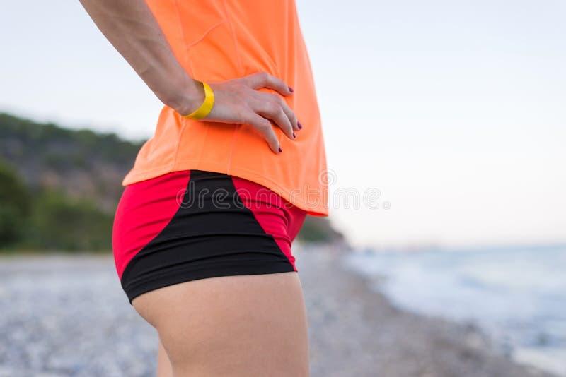 Actieve levensstijl Buit slank meisje Het aanstoten op het strand Overzees stock fotografie