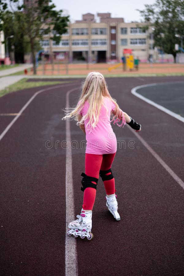 Actieve levensstijl in een moderne stad - actieve levensstijl in een moderne stad - modieuze meisjes rol-blading in een stadion royalty-vrije stock afbeelding