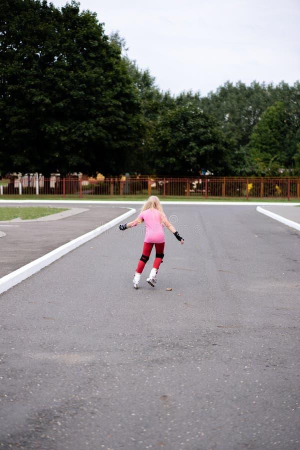 Actieve levensstijl in een moderne stad - actieve levensstijl in een moderne stad - modieuze meisjes rol-blading in een stadion stock foto