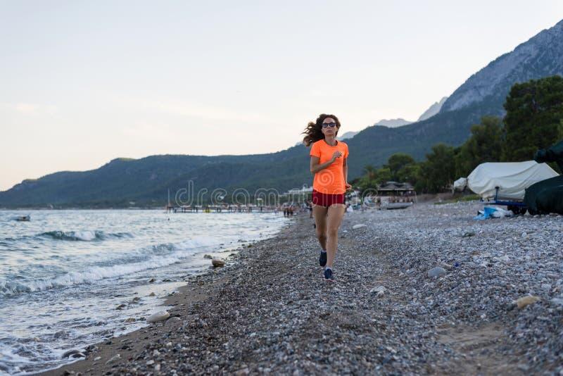 Actieve levensstijl: een slanke vrouw die langs het strand lopen stock afbeeldingen