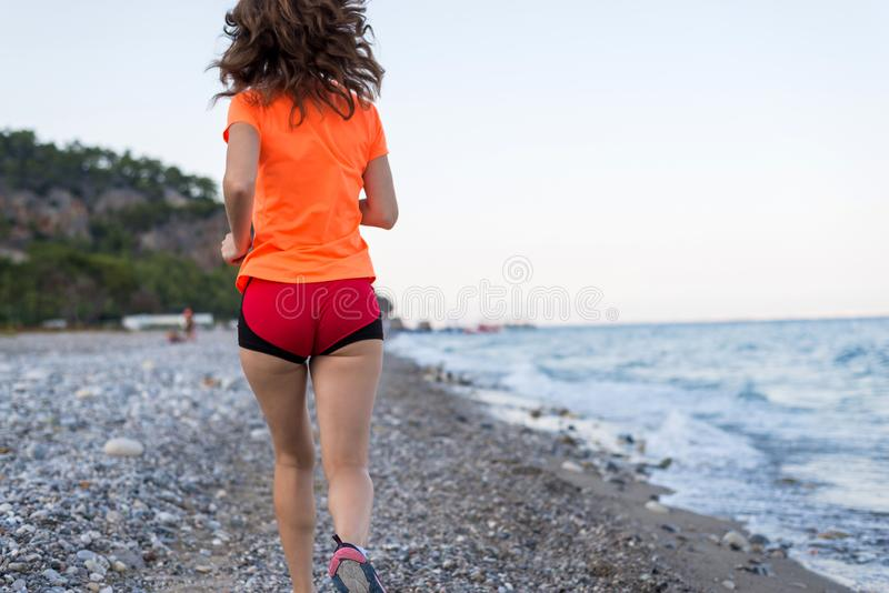Actieve levensstijl: een slanke vrouw die langs het strand lopen stock foto's