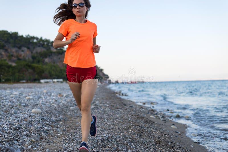 Actieve levensstijl: een slanke vrouwenlooppas langs het strand stock afbeelding