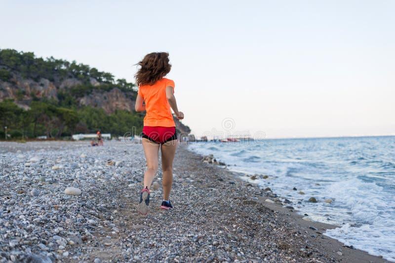Actieve levensstijl: een slanke vrouwenlooppas langs het strand royalty-vrije stock afbeeldingen