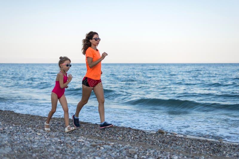 Actieve levensstijl: mamma en dochter die langs het strand in werking wordt gesteld stock afbeeldingen