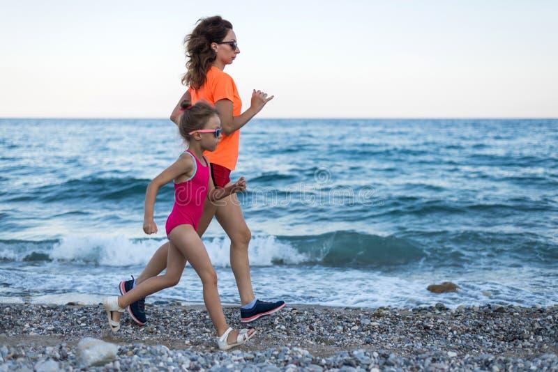 Actieve levensstijl: mamma en dochter die langs het strand in werking wordt gesteld stock fotografie