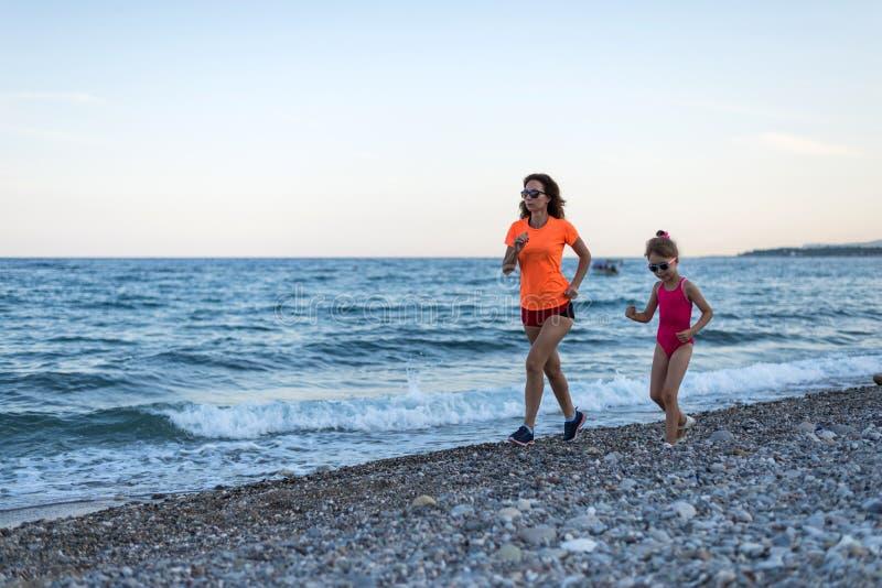 Actieve levensstijl: ochtendjogging langs het strand Mamma en dochter langs het strand in werking dat wordt gesteld dat royalty-vrije stock afbeelding