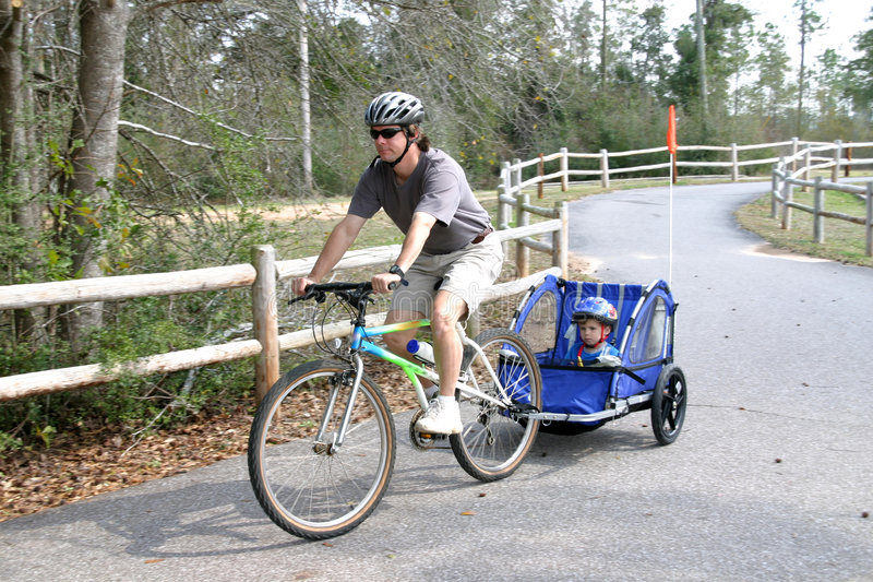 Actieve mens die zoon op fiets trekt stock afbeeldingen