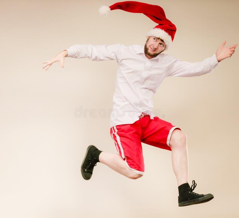 Actieve mens in en santahoed die dansen springen stock afbeelding