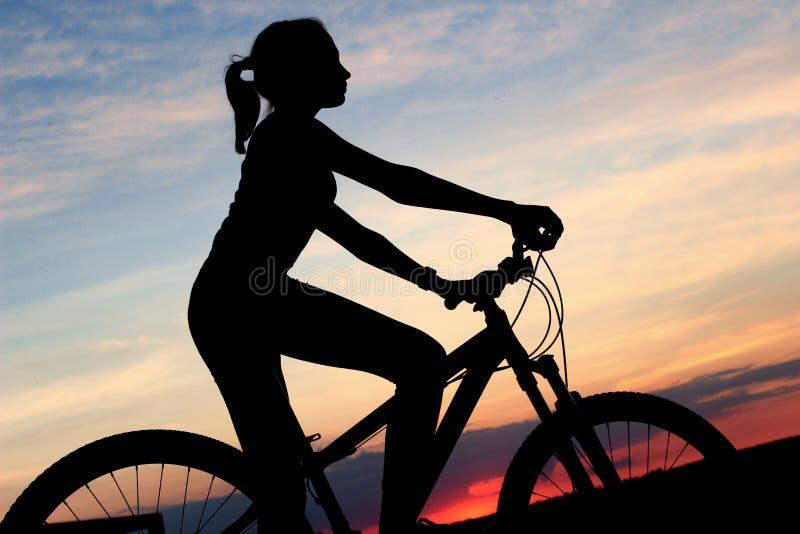 Actieve mensen, sport, aardconcept Jonge meisjeszitting op een fiets over mooie zonsondergangachtergrond stock foto's