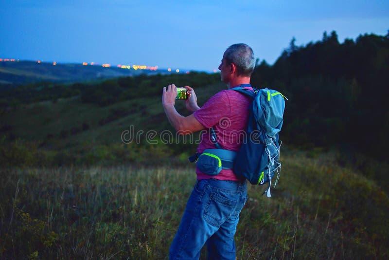 Actieve midden oude mens die zich op heuvel met rugzak bevinden, die beeld van bergenlandschap nemen tijdens schemering Mens die  stock afbeeldingen