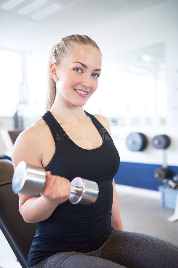 Actieve Mooie Vrouw het Opheffen Gewichten in de Gymnastiek stock afbeelding