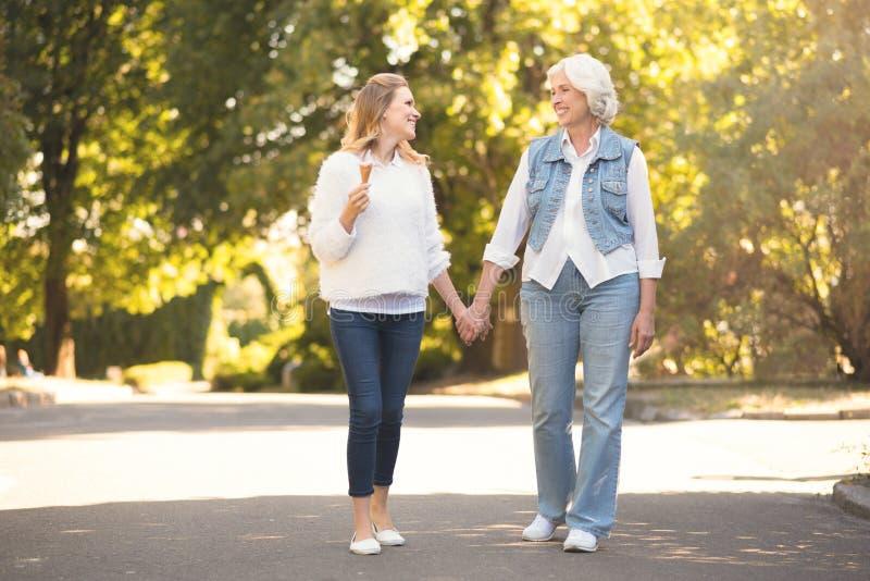 Actieve oude vrouw die met dochter in openlucht lopen stock foto's