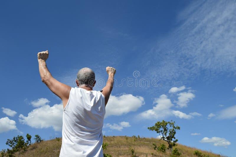 Actieve oudere mens met wapens omhoog in teken van succes of voltooiing op de heuvel stock afbeelding