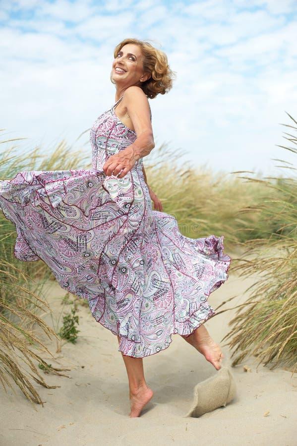 Actieve oudere vrouw die bij het strand dansen stock afbeeldingen