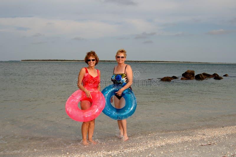 Actieve oudere vrouwen bij strand stock afbeelding