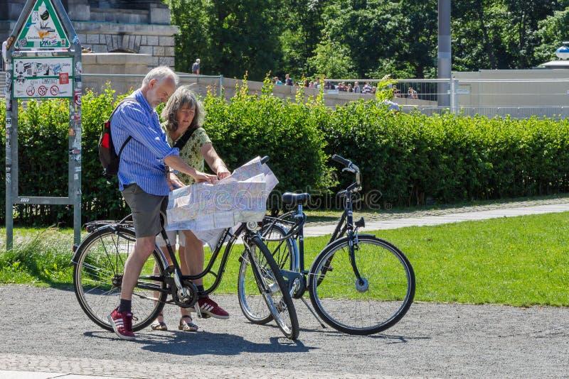 Actieve oudsten die op fietsen kaart op de straten van Berlijn bekijken stock foto's
