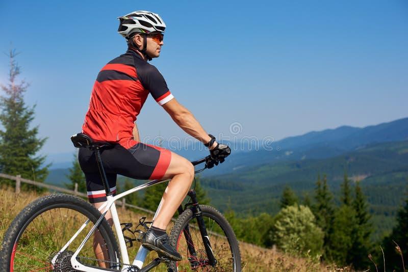 Actieve professionele sportmanfietser tegengehouden fiets bovenop heuvel stock fotografie