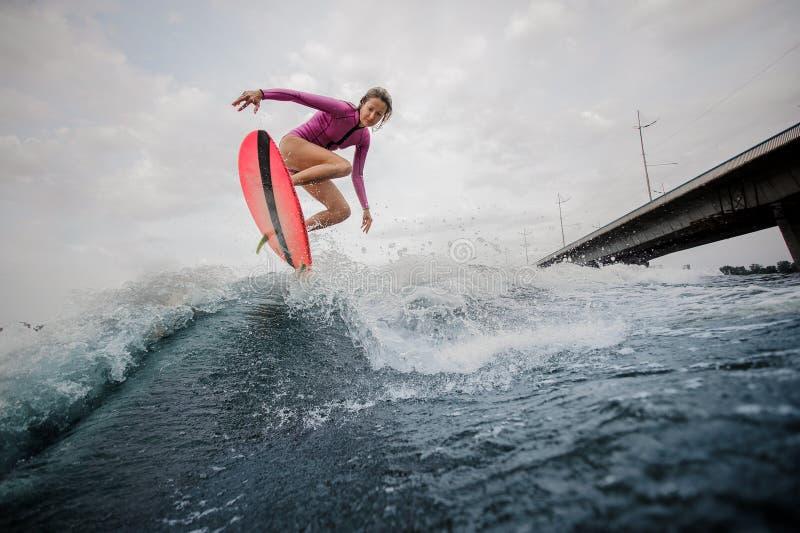 Actieve slanke vrouw die op de blauwe golf tegen de grijze hemel springen royalty-vrije stock afbeeldingen