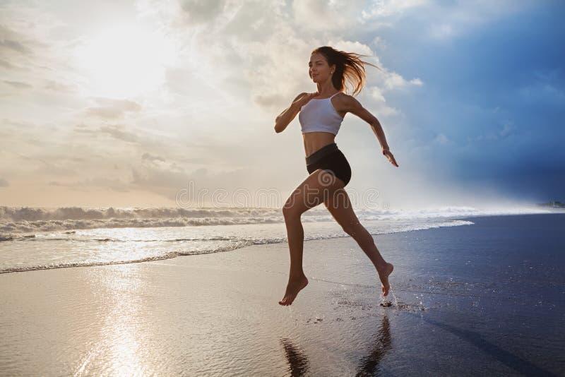 Actieve sportieve die vrouw langs zonsondergang oceaanstrand in werking wordt gesteld Sportenachtergrond royalty-vrije stock foto's