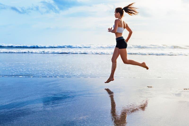 Actieve sportieve die vrouw langs zonsondergang oceaanstrand in werking wordt gesteld Sportenachtergrond royalty-vrije stock foto