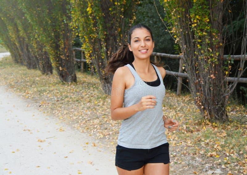 Actieve sportieve jonge agentvrouw die in het park lopen Glimlachende agentatleet die in openlucht opleiden stock foto's