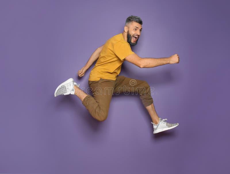 Actieve springende mens op kleurenachtergrond royalty-vrije stock afbeelding