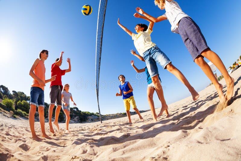Actieve tienerjaren die strandvolleyball in de zomer spelen stock foto's
