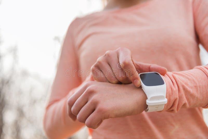 Actieve vrouw die het klaar plaatsen smartwatch als geschiktheidsmonitor krijgen slimme horloge lopende atleet die voor cardiotra stock foto's